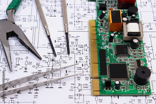 Fotografie, Obraz  Printed circuit board and precision tools on diagram of electronics, technology