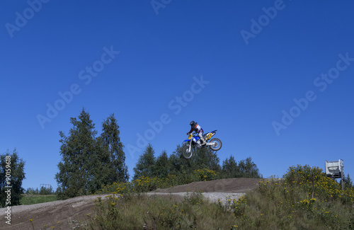Foto op Plexiglas Motorsport A person jumping with his motorcycle with the track and some threes in the background on a blue sky