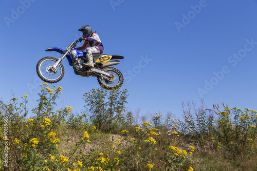 A man jumping with his motorcycle from a low angle and vegetation in the foreground