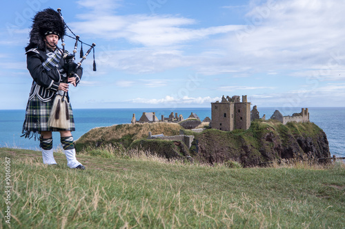 Traditional scottish bagpiper in full dress code at Dunnottar Castle in Stonehav Canvas Print