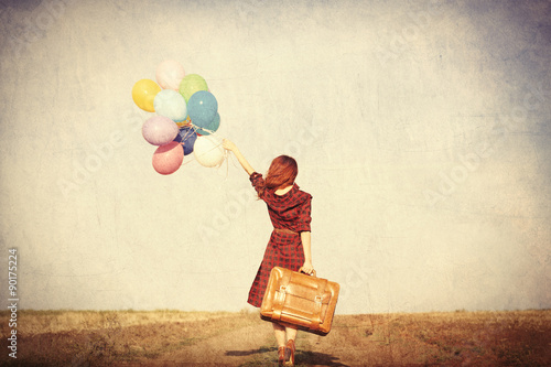 Foto  girl with multicolored balloons and bag