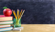 canvas print picture apple on books with pencils and empty blackboard - back to school