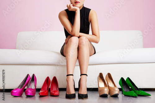 Fotografia  Woman thinking on the sofa with many shoes