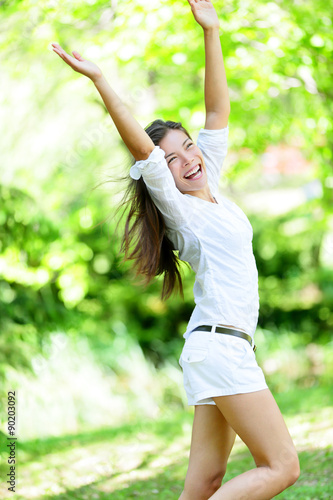 Excited young woman with arms raised standing in park. Happy mixed race Asian / Caucasian female is enjoying on sunny day. She is in casuals.