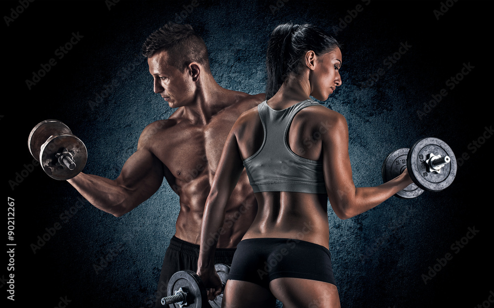 Fototapeta Athletic man and woman with a dumbells.