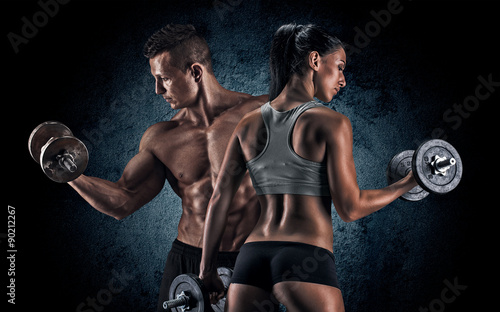 obraz lub plakat Athletic man and woman with a dumbells.