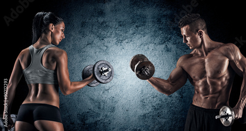 Photo sur Toile Fitness Athletic man and woman with a dumbells.