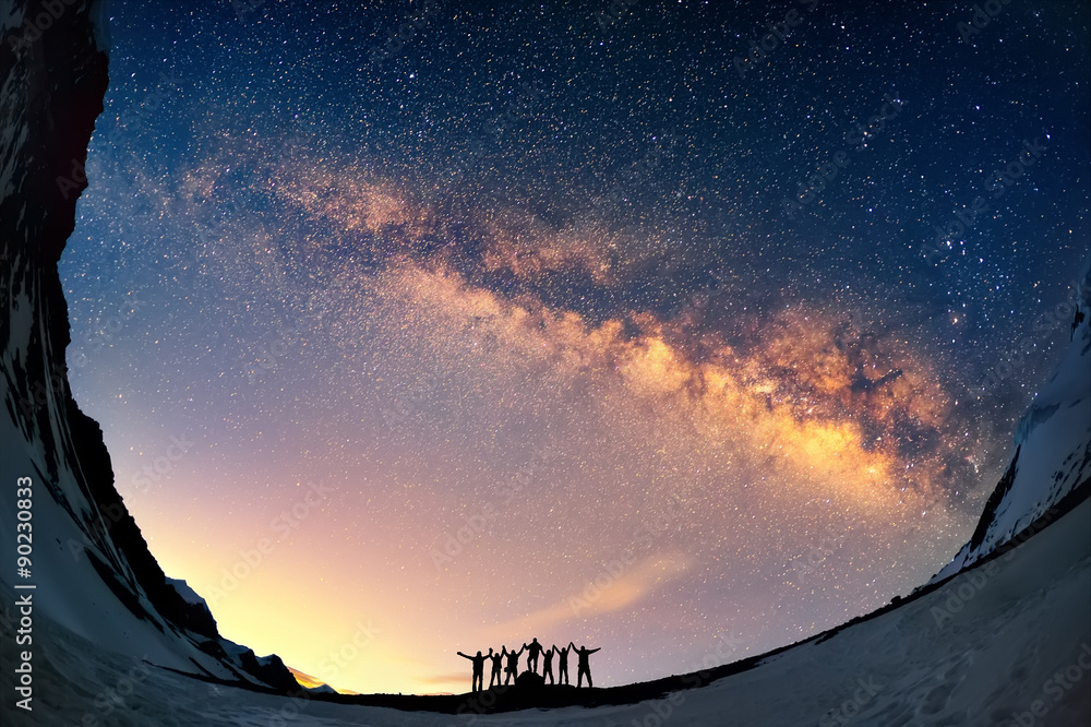 Fototapety, obrazy: Teamwork and support. A group of people are standing together holding hands against the Milky Way in the mountains.