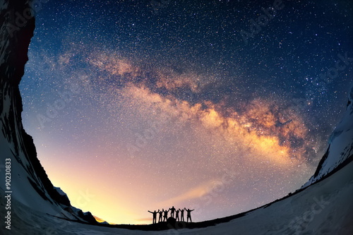 Obraz Teamwork and support. A group of people are standing together holding hands against the Milky Way in the mountains.  - fototapety do salonu