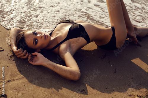 Obraz sexy girl with dark hair and tanned skin posing on beach - fototapety do salonu