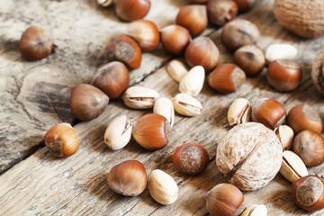 Fototapeta samoprzylepna Walnuts, hazelnuts and pistachios on a wooden table, toned image