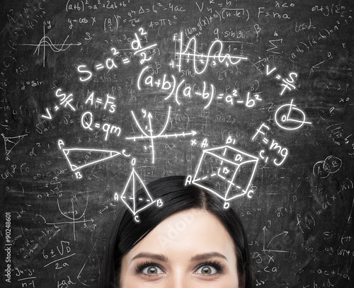 Fotografia A forehead of the brunette lady and maths formulas are drawn on the black chalkboard