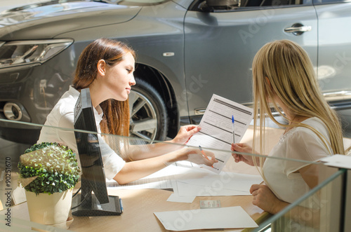 Fototapeta Девушки подписывают контракт на покупку нового автомобиля obraz