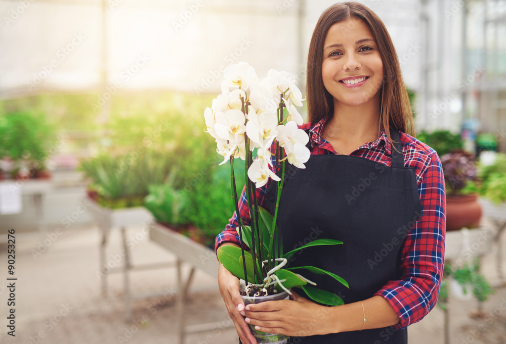 Fototapeta Smiling happy young florist in her nursery