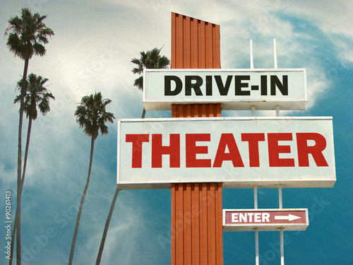 aged and worn vintage photo of drive in theater sign with palm trees