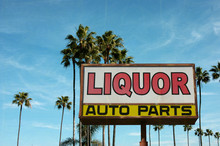 Aged And Worn Vintage Photo Of Liquor And Auto Parts Sign With Palm Trees