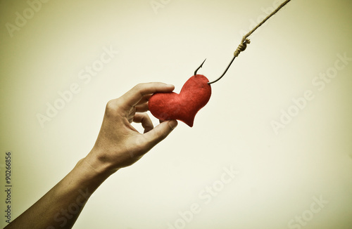 Fényképezés  hand trying to catch a red heart on a fish hook - Love trap concept