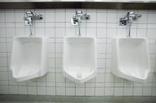 Three White Urinals In Men's Bathroom
