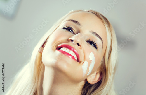 Obraz smiling woman applying creme at home - fototapety do salonu