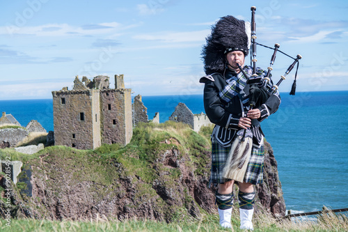 Billede på lærred Traditional scottish bagpiper in full dress code at Dunnottar Castle in Stonehav
