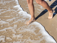 Woman's Legs Stepping In The Sea