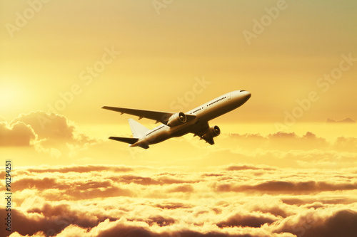 Fotografering  Airplane in the sky at sunset