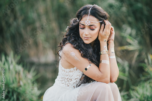 Beautiful young woman with long curly hair dressed in boho style dress posing ne Poster