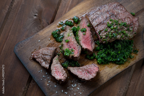 Sliced medium rare grilled beef barbecue steak with chimichurri Poster