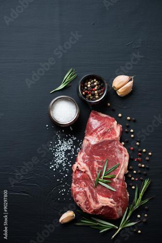 Raw ribeye beefsteak with seasonings, black wooden background Canvas Print