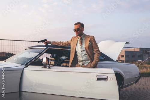 Retro 1970s gangster with pistol leaning against vintage car. Canvas Print