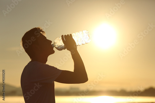 Canvas Print Fitness man silhouette drinking water from a bottle