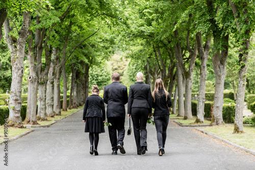 Leinwand Poster Familie läuft auf Allee im Friedhof in Trauer mit Blumen in der Hand