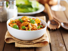 Bowl Of Bowtie Pasta With Meat, Tomato Sauce And Basil Leaves Sitting On Napkin