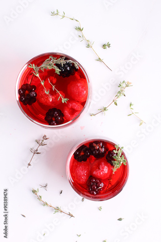 Foto op Canvas In het ijs glass of berry drink with fresh fruits on marble table.