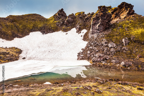 Fotografie, Obraz  Big unmelted in July snowfield reflected in water