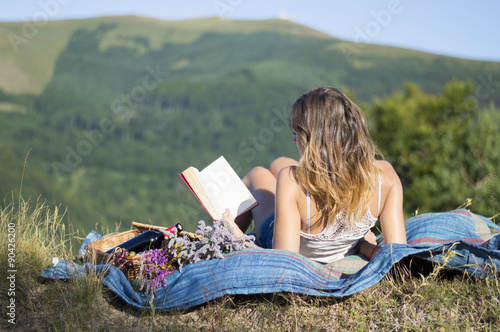 Fotografie, Obraz  Girl laying on a blanket and reading a book on a picnic in the f