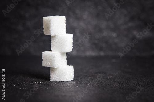 Fotografie, Obraz  cloose up white sugar cubes on black stone plate background
