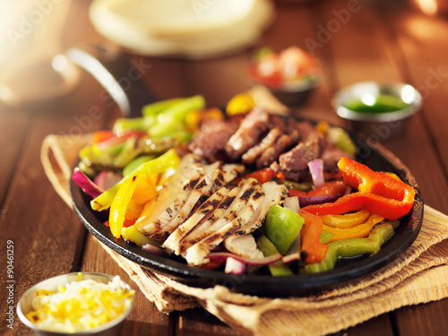Photo  mexican steak and chicken fajitas in iron skillet with bell peppers and onion sh