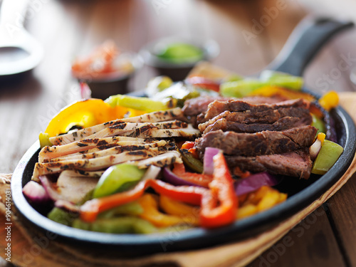 Tela  steak and chicken fajitas close up in cast iron fajita skillet