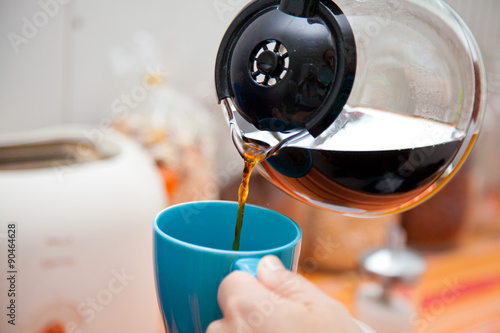 Fotografie, Obraz  woman pouring coffee pot  into coffe mug