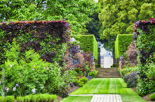 obraz lub plakat Formal summer garden with grass path to stone stairs and iron gate