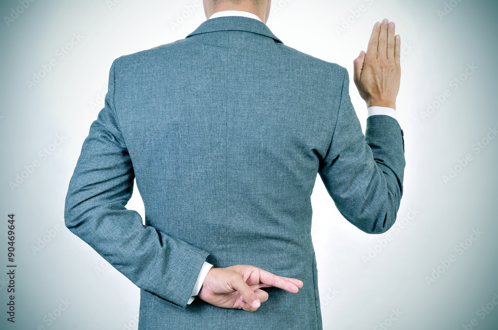 Valokuva  young man swearing an oath, crossing his fingers in his back