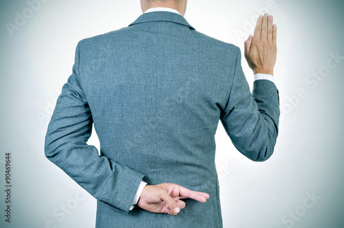 young man swearing an oath, crossing his fingers in his back Fototapet