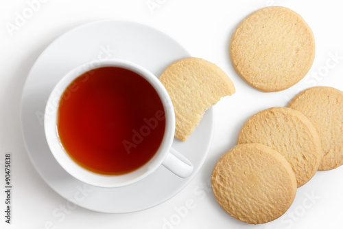 In de dag Koekjes White cup of tea and saucer with shortbread biscuits from above.