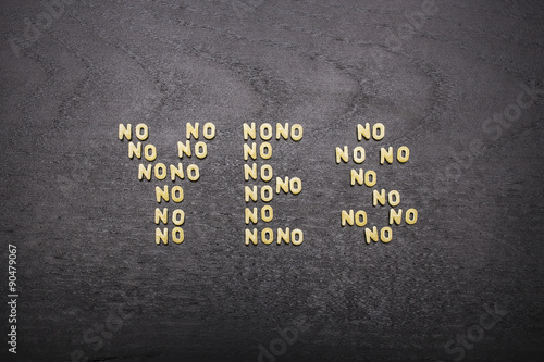 Photo The answer  yes made up of a set of words no, with small pasta letters on a dark background of a wooden board, showing the hidden meaning and ambiguity of the agreement