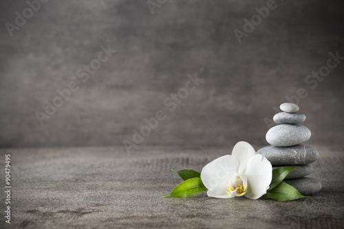 Foto op Plexiglas Orchidee White orchid and spa stones on the grey background.