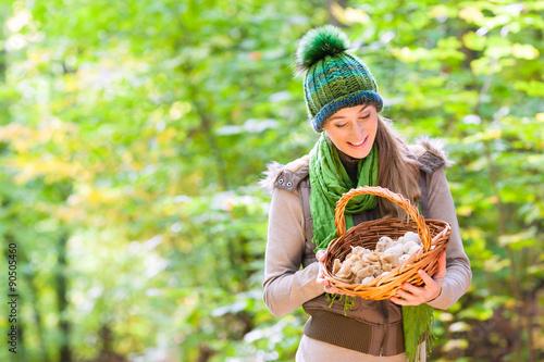 Fotografía  Frau mit Korb voller Pilze beim Sammeln im Wald