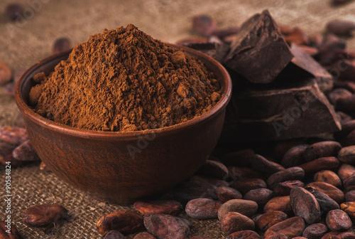 Fotografía  cocoa powder in a brown ceramic bowl, raw cocoa beans in the pee