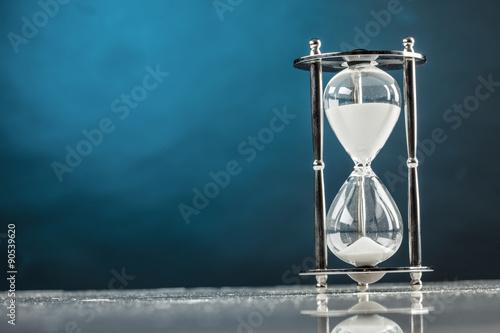 Fotografie, Obraz  Clessidra di vetro su sfondo azzurro