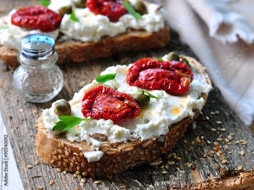 Fotografía  toast of rye bread with different seeds with ricotta cheese, sun-dried tomatoes, capers, parsley and olive oil